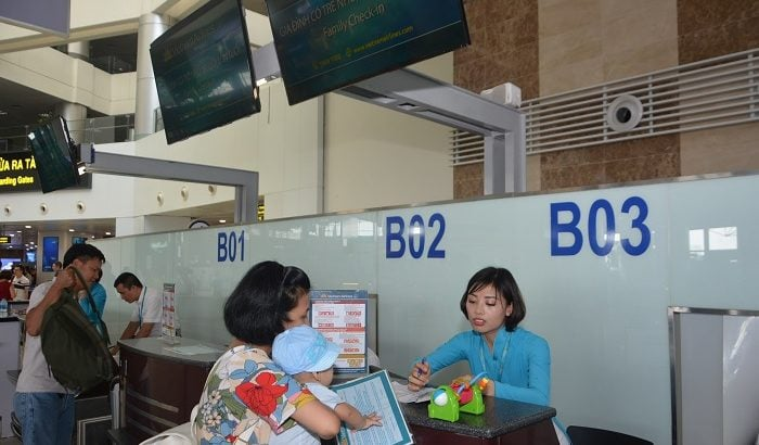 Gia đình có trẻ nhỏ làm dịch vụ Family check-in tại quầy